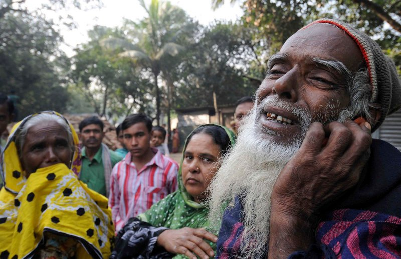 A Bangladeshi man grieves as he looks for his son's body Monday outside a garment factory where a fire killed at least 112 people Saturday on the outskirts of Dhaka, Bangladesh.