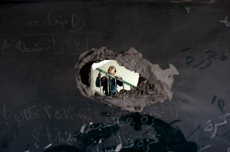 A Palestinian schoolgirl is seen through a hole in a blackboard Monday, days after an Israeli strike hit a school in Gaza City. Readers differ on how to reach resolution to the Israeli-Arab conflict.