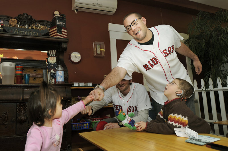 Natalie Morin gives fist bumps to pitcher Chris Carpenter and outfielder Ryan Kalish while her brother Thomas looks on at the Briarwood Children's House in Lyman Tuesday morning.