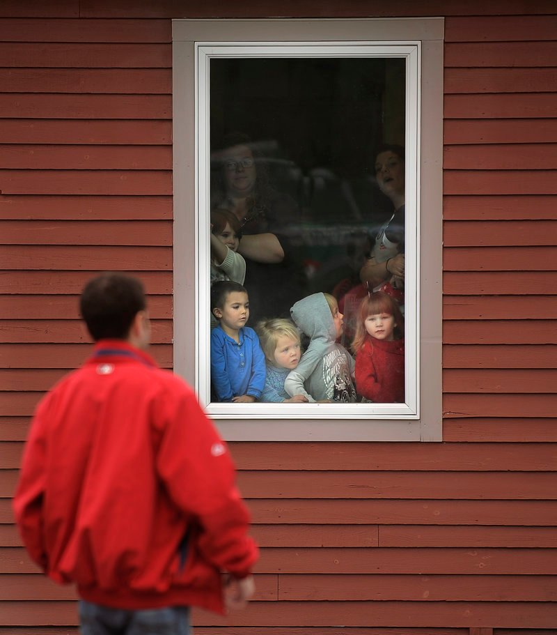 Children at Briarwood Children's House gather by a window waiting for Wally the Green Monster and his baseball buddies late Tuesday morning.