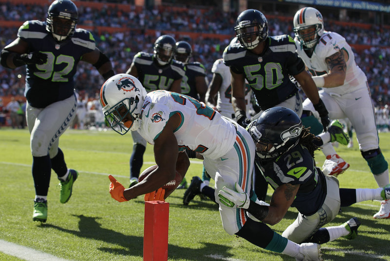 Reggie Bush, Miami running back, stretches into the end zone despite the efforts of Seattle safety Earl Thomas (29) during Sunday's victory that leaves Miami at 5-6 and still in contention for an AFC wild-card berth as the season enters the homestretch.