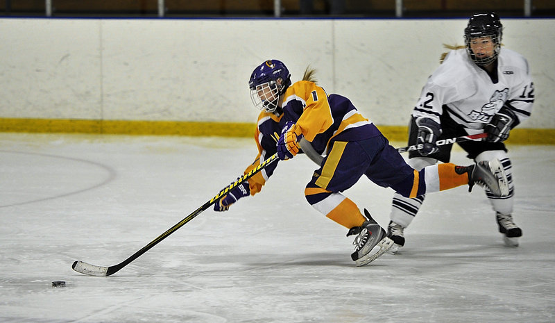 Sophia Giancotti of Cheverus gets tripped by Katie Rutherford of Portland-Deering in an 8-8 tie Wednesday night at Portland Ice Arena. Giancotti scored the first of three short-handed goals in the third period for the Stags.
