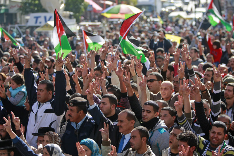 People wave Palestinian flags during a rally supporting the Palestinian U.N. bid for nonmember observer state status in the West Bank city of Ramallah on Thursday.