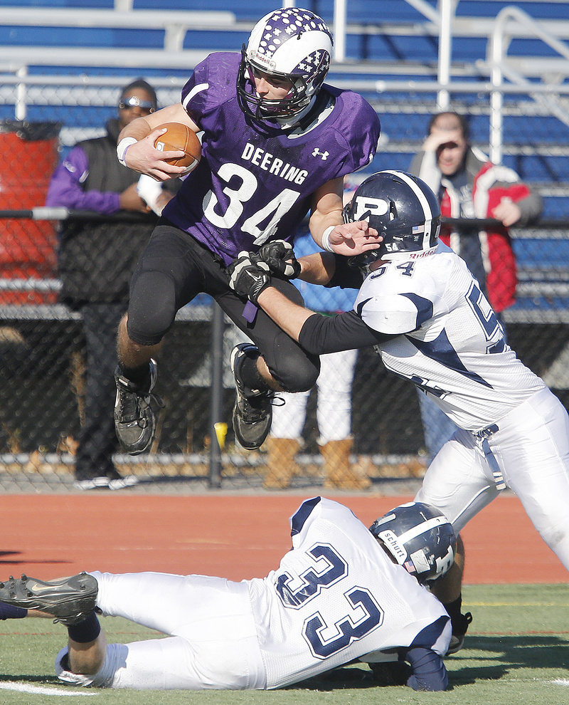 Kenny Sweet, who carried 22 times for 249 yards for Deering, is hit by Tate Gale of Portland, right, while trying to leap over Dominic Fagone of the Bulldogs. Deering won 28-14 in the annual Thanksgiving game.