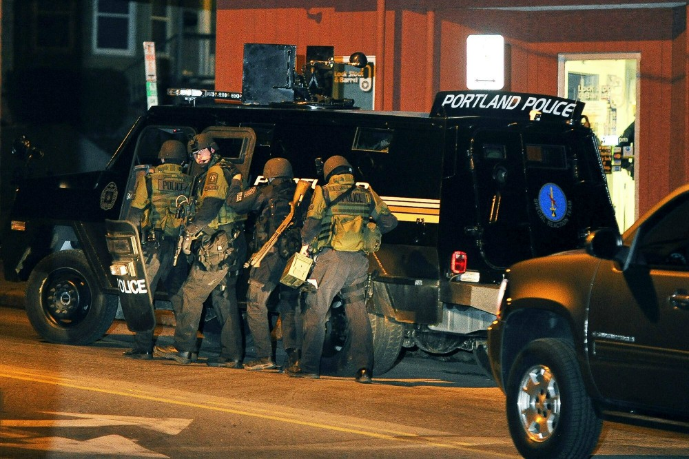 Thursday, December 22, 2011. The Portland Police Special Reaction Team members start their movement outside the Lock, Stock and Barrel toward the apartment building containing the suspect who is with a stand off with police on St. John Street.