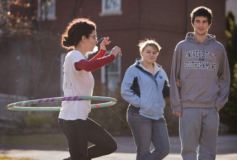 USM student, and protest organizer Jordana Avital, smokes while spinning a hula hoop during a protest of a proposed smoking ban on USM campuses at the Gorham campus on Monday. Fellow students Michaela Thibeault and Richar Cost look on, at right.
