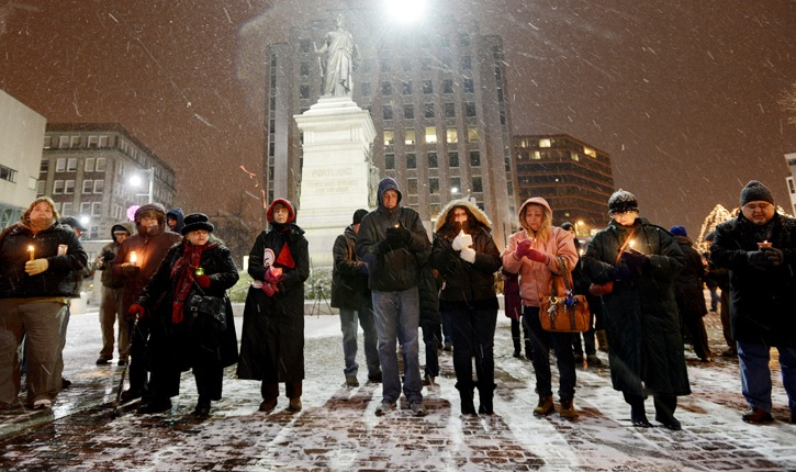 A crowd braves the weather to participate in a candlelight vigil in Portland's Monument Square for the victims of Friday's shooting in Newtown, Conn.