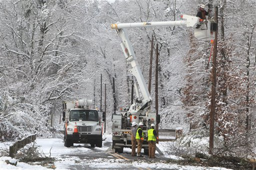 An Entergy Arkansas Inc., crew works to restore power to customers on Whittington Avenue near the entrance to Hot Springs National Park, Thursday, Dec. 27, 2012, in Hot Springs, Ark. A Christmas Day storm dumped between 6 to 15 inches of snow knocking out power to about half of the 61,000 customers in Garland County. (AP Photo/The Sentinel-Record, Richard Rasmussen)