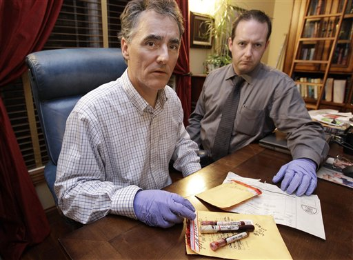 In this photo taken Friday, Nov. 30, 2012, in Chicago, Cook County Sheriff Tom Dart, left, and sheriff's detective Jason Moran are photographed with three recently discovered vials of mass murderer John Wayne Gacy's blood. The sheriff�s office is creating DNA profiles from the blood of Gacy and other executed killers and putting them in a national DNA database of profiles created from blood, semen, or strands of hair found at crime scenes and on the bodies of victims. What they hope to find is evidence that links the long-dead killers to the coldest of cold cases and prompt authorities in other states to submit the DNA of their own executed inmates and maybe evidence from decades-old crime scenes to help them solve their own cases. (AP Photo/M. Spencer Green)