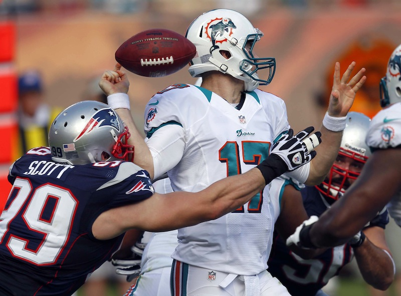 Miami Dolphins quarterback Ryan Tannehill (17) fumbles the ball after being hit by New England Patriots defensive end Trevor Scott (99) during the first half of an NFL football game, Sunday, Dec. 2, 2012 in Miami. (AP Photo/Wilfredo Lee) NFLACTION12;