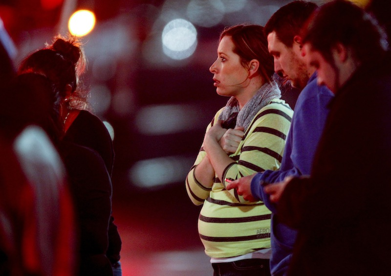 Onlookers gather outside Clackamas Town Center in Clackamas, Ore., where a gunman opened fire at a shopping mall Tuesday.