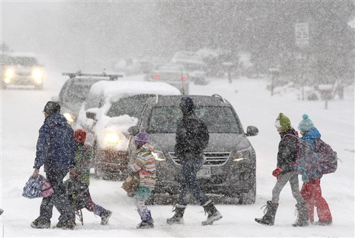 Elementary school students escorted by parents cross a snowy street en route to school as a blizzard dropped snow over Boulder, Colo., on Wednesday. The storm is on track to hit the central plains and Midwest on Thursday.