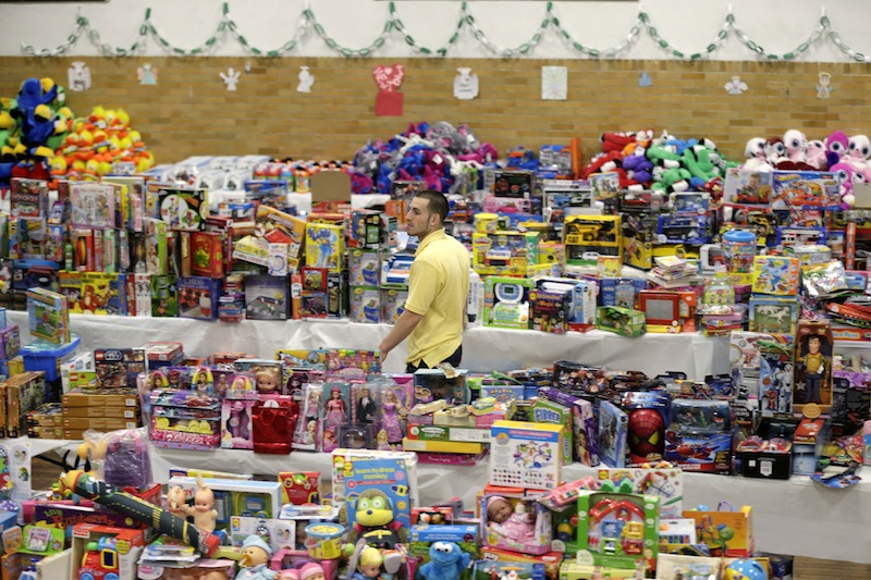 Volunteer Anthony Vessicchio of East Haven, Conn., helps to sort tables full of donated toys at the town hall in Newtown, Conn., Friday, Dec. 21, 2012. (AP Photo/Seth Wenig)