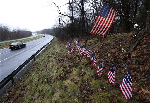 A makeshift memorial of 27 small and one large American flag stands by the side of Highway 84 near the Newtown, Conn., town line on Monday.