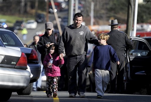 Parents leave a staging area after being reunited with their children following a shooting at the Sandy Hook Elementary School in Newtown, Conn., on Friday.