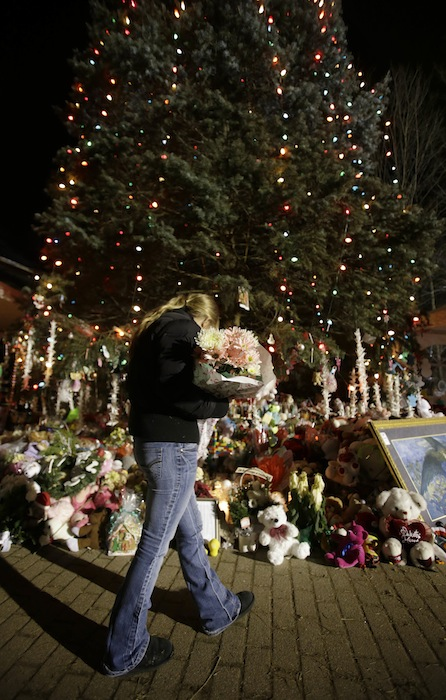 In this Thursday, Dec. 20, 2012 file photo, a woman with flowers walks past a Christmas tree which has become a memorial to the Newtown shooting victims in Newtown, Conn. In the wake of the shooting, the grieving town is trying to find meaning in Christmas. (AP Photo/Seth Wenig)