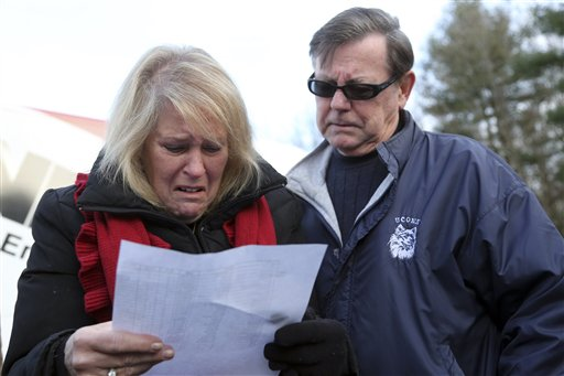 Kathy Murdy, left, and her husband, Rich, react Saturday in Newtown, Conn., as they look at the list of victims of the Sandy Hook Elementary School shooting.