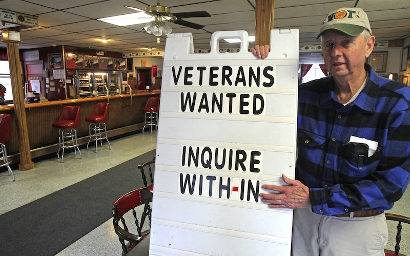 "In this Wednesday, Dec. 19, 2012, Legion Post 3 Commander Dick Harlow poses with a sign in Montpelier, Vt. The American Legion post in Vermont's capital city has a simple method to help attract new members: A sign in the Main Street doorway says ""members wanted."" They still get new members, sometimes veterans of Iraq and Afghanistan, but few of them are young, most are in their 40s or even older. (AP Photo/Toby Talbot)"