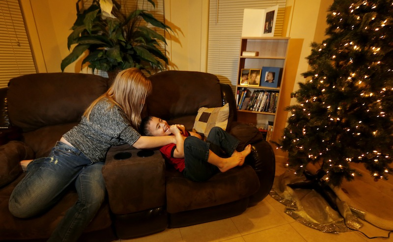 McKenna Pope, 13, left, plays with her brother Gavyn Boscio, 4, in their home in Garfield, N.J. on Thursday, Dec. 6, 2012. Pope started a petition demanding the toy company Hasbro make its Easy-Bake Oven more boy friendly. She was inspired to do so when Gavyn put the oven on his Christmas wish list and she and their mother, Erica Boscio, found the toy only available with girls on the packaging and in pink or purple colors. The petition garnered more than 30,000 signatures in a little more than a week. (AP Photo/Julio Cortez)