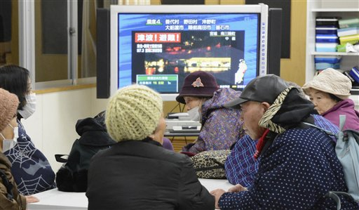 Tsunami evacuees watch TV news flashing a tsunami warning at their shelter at Takata Junior High School that stands on a higher ground in Rikuzentakata in Iwate Prefecture on Friday after a strong earthquake struck off the coast of northeastern Japan.