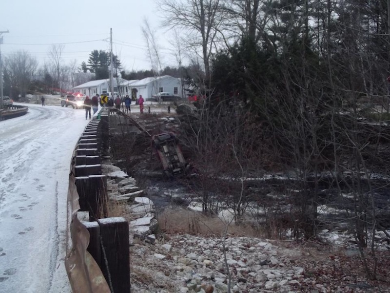 This photo provided by the Lebanon Rescue Department's Facebook page shows an SUV that smashed through a guardrail Christmas morning and settled on a riverbank. The driver escaped injury.
