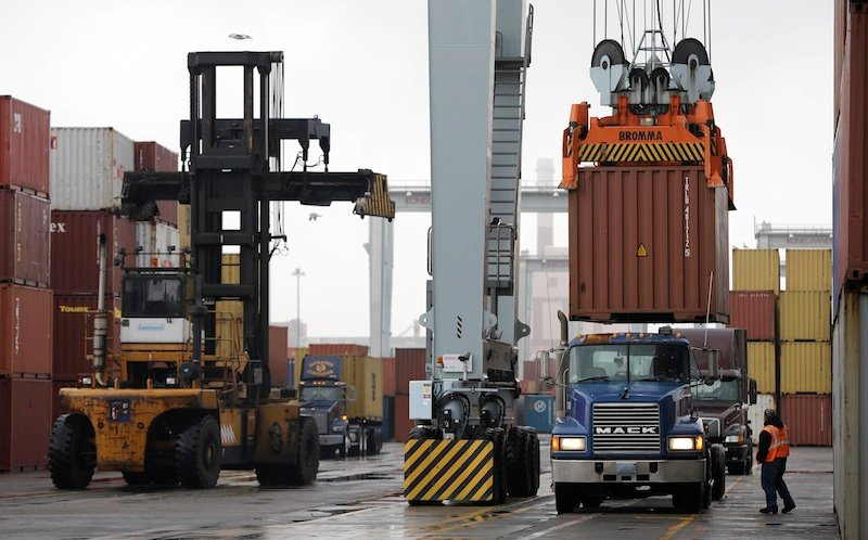 In this Dec. 18, 2012 file photo, a truck driver watches as a freight container, right, is lowered onto a tractor trailer by a container crane at the Port of Boston in Boston. The crane and a reach stacker, left, are operated by longshoremen at the port. The longshoremen's union may strike if they are unable to reach an agreement on their contract, which expires Dec. 29, 2012. A walkout by dock workers represented by the International Longshoremen's Association would bring commerce to a near halt at ports from Boston to Houston. (AP Photo/Steven Senne, File)