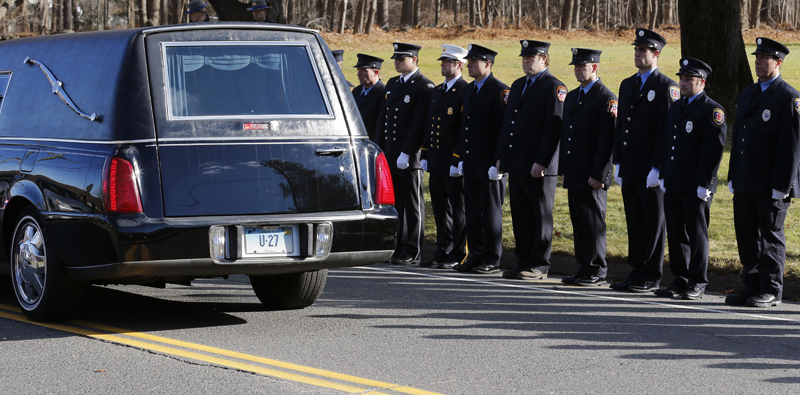 Firefighters stand together as a hearse carries the casket of Daniel Gerard Barden, 7, who dreamed of being a firefighter.