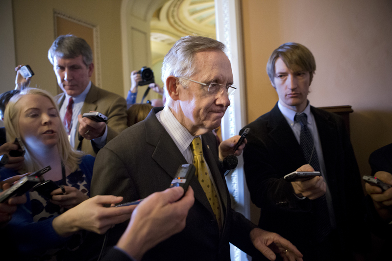 Senate Majority Leader Harry Reid, D-Nev., retreats to a closed-door meeting with fellow Democrats as he and Senate Minority Leader Mitch McConnell, R-Ky., work to negotiate a legislative path to avoid the so-called