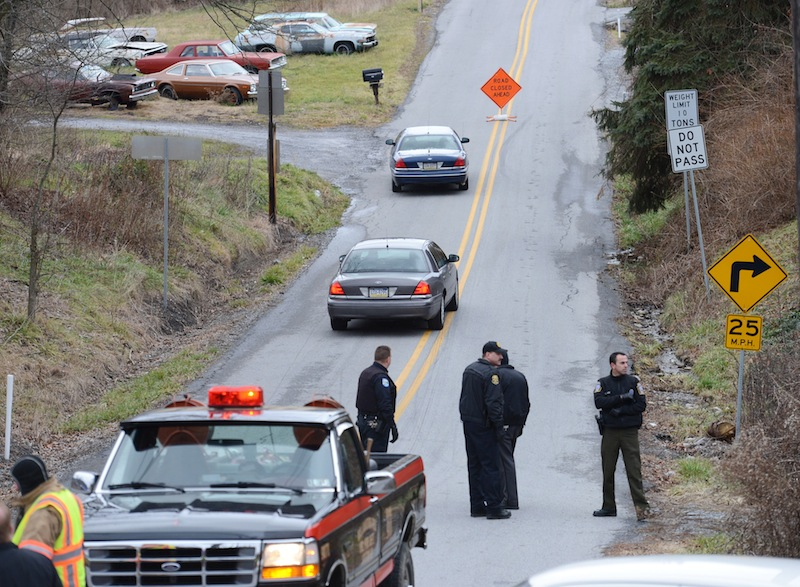 Local law enforcement block off road along Rt. 22 near the Canoe Creek State Park, Pa. while investigating a shooting on Friday, Dec. 21, 2012. The suspect fired at troopers responding to Friday morning's shootings in Frankstown Township, about 70 miles west of Harrisburg. The fleeing gunman then crashed head-on into a trooper's car and got out of his truck and shot again at police, who returned fire and killed him. Blair County District Rich Consiglio says the gunman killed two men and one woman. (AP Photo/Altoona Mirror, J.D. Cavrich)