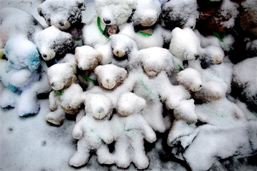 Snow-covered stuffed animals with photos attached sit at a memorial in Newtown, Conn. Tuesday, Dec. 25, 2012. People continue to visit memorials after gunman Adam Lanza walked into Sandy Hook Elementary School in Newtown, Friday, Dec. 14, and opened fire, killing 26, including 20 children, before killing himself. (AP Photo/Craig Ruttle)