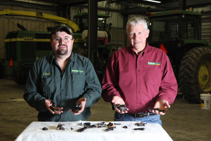 Hammond Tractor Company co-owner Gary Hammond, right, and employee Chad Tibbetts hold pieces of destroyed firearms in Fairfield on Friday. In the wake of the Newtown, Conn. shooting, Hammond Tractor – a hunter and gun owner – was offering to accept and destroy firearms from local citizens. He has since rescinded that offer.