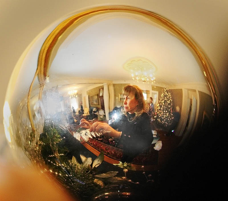 Maggie Kelley is reflected in a large silver ball as she decorates a fireplace mantle on Tuesday at the Blaine House in Augusta.
