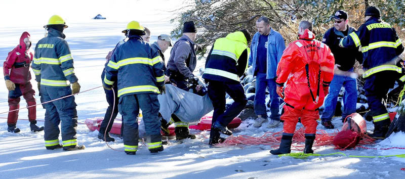 Firefighters from several area departments lift Tracy Scott, 47, of Mercer, who had fallen into the water of North Pond in Mercer on Tuesday, onto a stretcher. Scott had gone onto the thin ice to rescue a dog and broke through the ice.