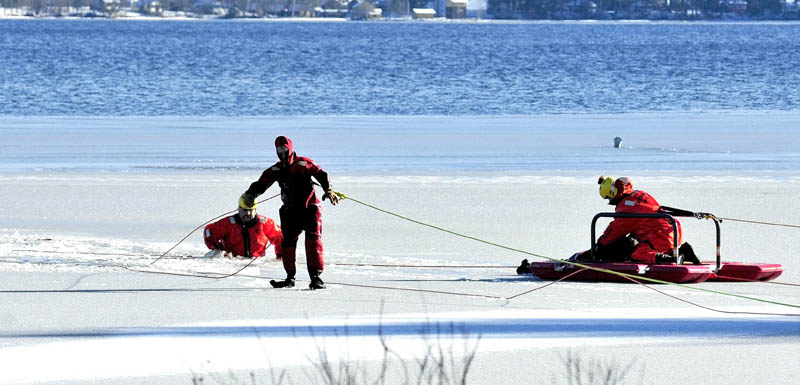 Firefighters in survival suits bring Tracy Scott, 47, of Mercer, to shore in a rescue sled, after she went out on thin ice on North Pond in Mercer and plunged in the water while attempting to rescue a dog on Tuesday.