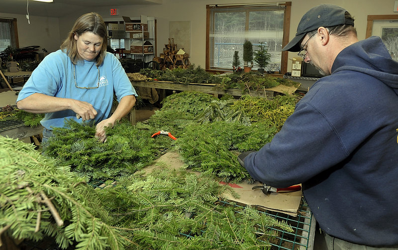 Cindy Carroll, perennial buyer, and Larry Peterson, manager of O'Donal's in Scarborough, make wreaths for sale that will be decorated with ribbons and a variety of seasonal items.