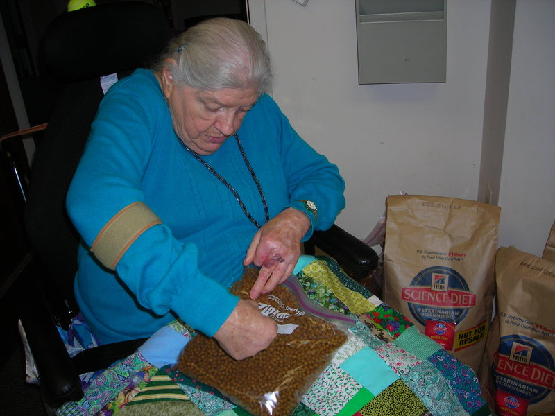 "Dottie Carter helps package pet food that will be delivered, along with regular Meals on Wheels dinners, to seniors who have pets. ""I enjoy my job (volunteering) to help the animals,"" she said."