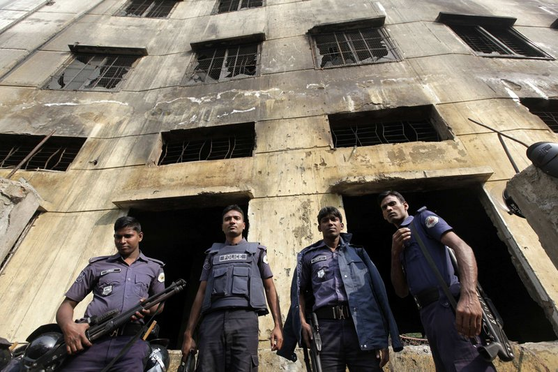 Police officers gather in front of a burned-out garment factory in Bangladesh. A fire last Saturday raced through the building, killing 112 workers and putting new focus on the working conditions for many overseas workers.