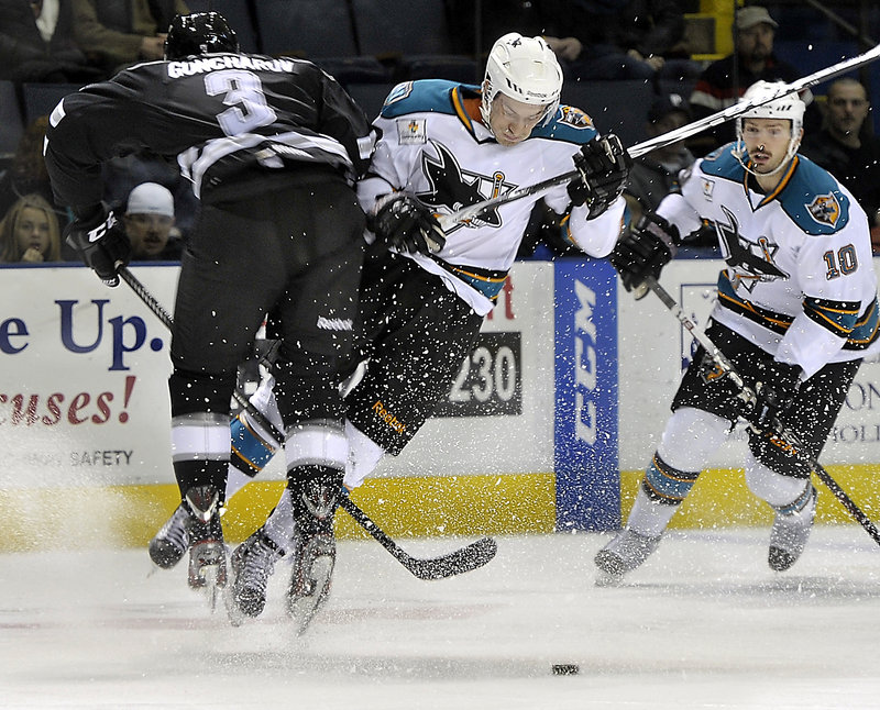 Pirates defenseman Maxim Goncharov, left, checks Worcester's Curt Gogol as Frazer McLaren of the Sharks looks on Friday night at the Cumberland County Civic Center.