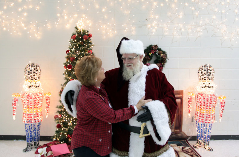 John Parks, in the role of Santa Claus, receives a welcome from school principal Carol Winters while greeting students last week at Newton Lee Elementary School in Ashburn, Va.