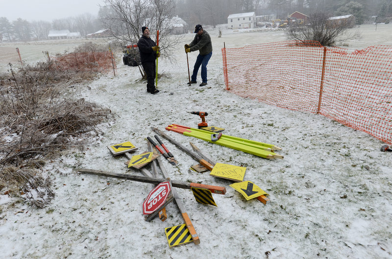 Brian Williams, left, and Joe Sayah, members of the Windham Drifters Snowmobile Club, erect a fence between a trail and a field as the club gets ready for the upcoming riding season.