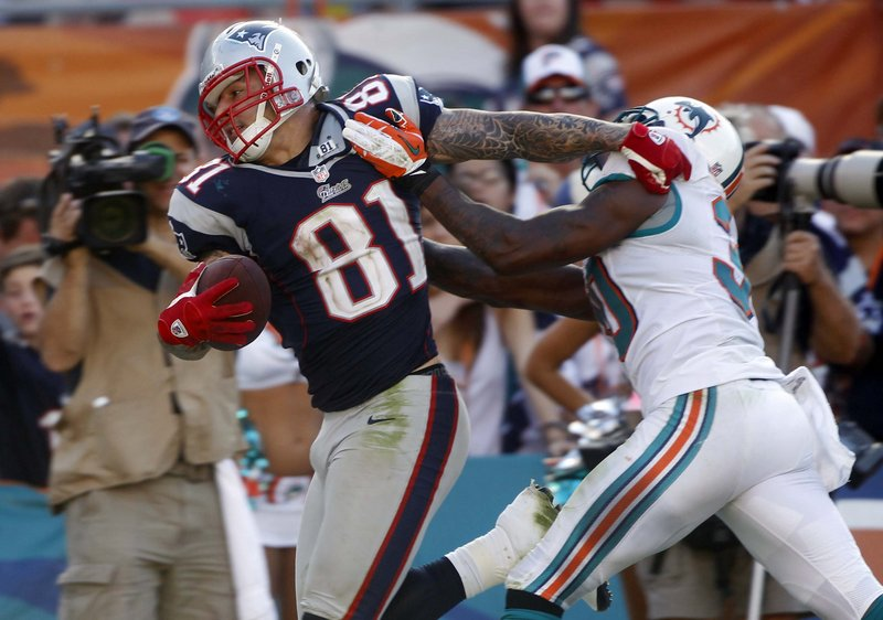 Patriots tight end Aaron Hernandez tries to stiff-arm Dolphins safety Chris Clemons during Sunday's game at Miami, won by the Patriots, who are again bound for the postseason.
