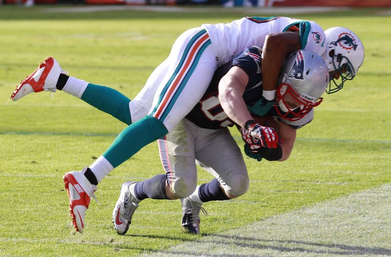 Wes Welker hangs onto a sideline pass despite the best efforts of Miami defensive back R.J. Stanford during second-half action of Sunday's Patriots-Dolphins game.