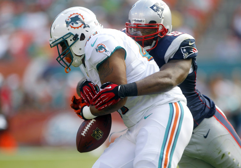 Jerod Mayo, New England linebacker, forces a fumble by Miami fullback Jorvorskie Lane, but the Dolphins recovered the ball during first-half action.