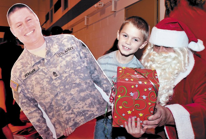 Colby Peacock of Yarmouth gets a present from Santa while holding a large photo he brought of his father, 1st Sgt. Michael Peacock, during a Christmas party for families of soldiers in Unit 488 serving in Afghanistan, in Waterville on Sunday.