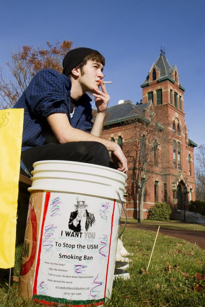USM freshman Joshua Thornberg smokes during a protest of a proposed smoking ban on USM campuses at the Gorham campus on Monday. Buckets like this one were made by protest organizers and placed around campus.