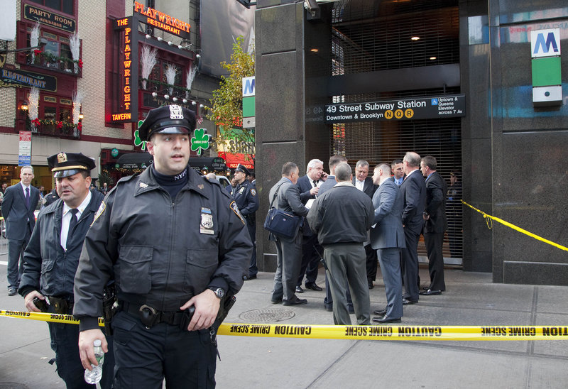 Police officers stand outside the Times Square subway station on Monday after the death of Ki-Suck Han. Police on Tuesday questioned a man suspected of pushing Han onto the tracks.
