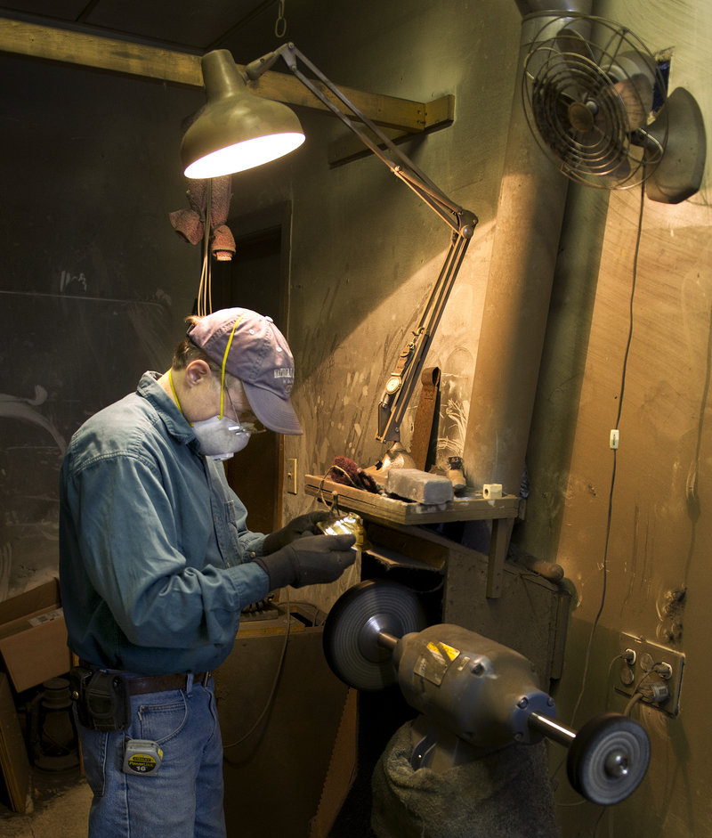 Mike Gutgsell owns The Polishing Shop, which adjoins Allen's lamp-repair shop in South Portland. He's shown here at his work station, using a polishing machine to restore a brass candlestick. The shops cater to a mostly local clientele, but have attracted customers from New York and California.