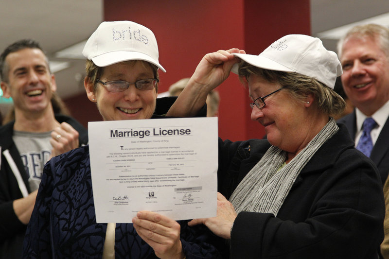 "Claudia Gorbman, left, and partner Pam Keeley both wear caps reading ""bride"" as they display their marriage license Thursday in Seattle."