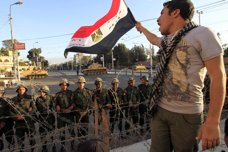 A protester waves an Egyptian flag in front of Republican Guard soldiers standing behind a barricade and guarding the presidential palace in Cairo on Friday.