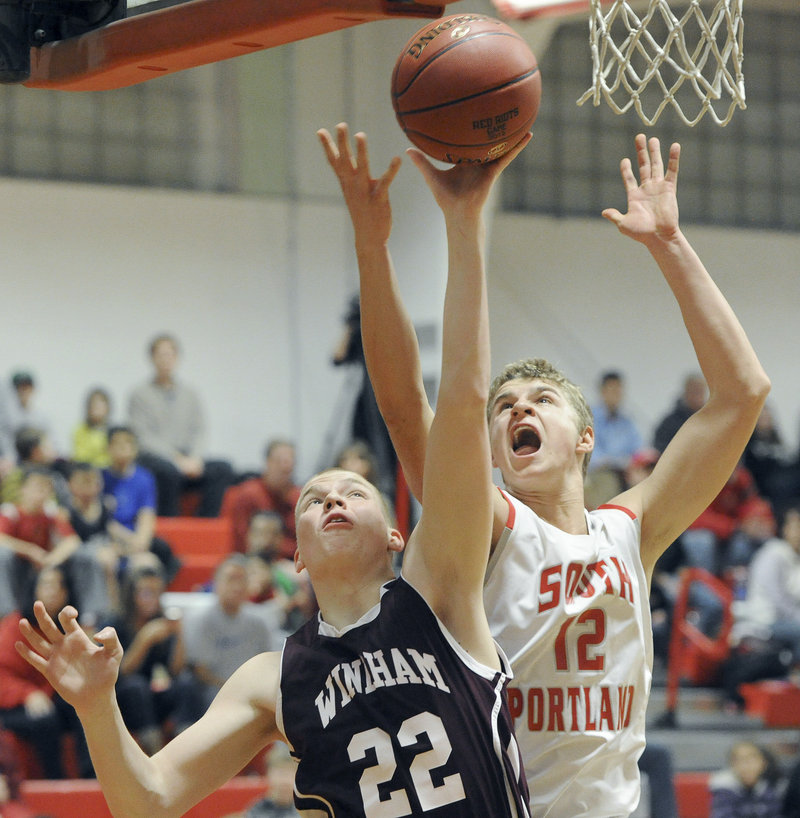 Dylan Weisser of Windham, left, pulls down a rebound in front of Ben Burkey of South Portland in Friday night's opener. South Portland beat the Eagles, 56-39.